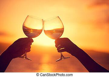 homem mulher, retinir, copos de vinho, com, champanhe, em, pôr do sol, céu dramático, fundo