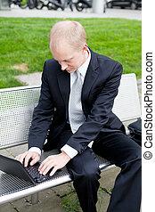 homem negócio, sentando, ao ar livre, trabalhando, com, caderno