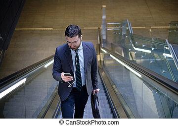 homem negócios, é, olhar, seu, telefone móvel, enquanto, é, ir trabalhar