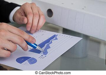 homem negócios, analisando, gráfico, escrivaninha