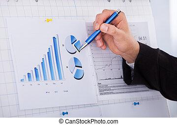 homem negócios, caneta, analisando, gráfico