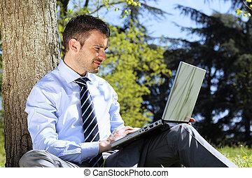 homem negócios, com, computador, em, um, parque, em, verão