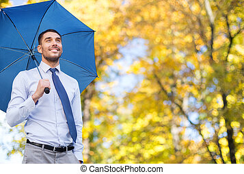homem negócios, com, guarda-chuva, sobre, outono, fundo