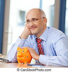 homem negócios, com, piggybank, olhando, escrivaninha