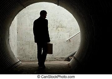 homem negócios, em, silueta, andar, em, um, escuro, túnel
