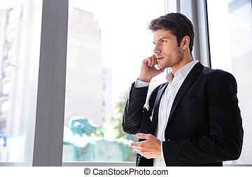 homem negócios, falando telefone móvel, perto, a, janela, em, escritório