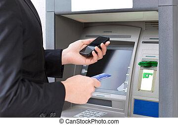 homem negócios fica, perto, a, atm, e, segurando, um, cartão crédito, e, telefone móvel, em, mãos