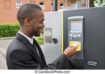 homem negócios, inserindo, bilhete, em, estacionamento, máquina