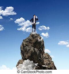 homem negócios, ligado, a, topo, de, um, alto, montanha
