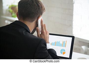 homem negócios, multitasking, falando telefone, enquanto, trabalhar, lapt