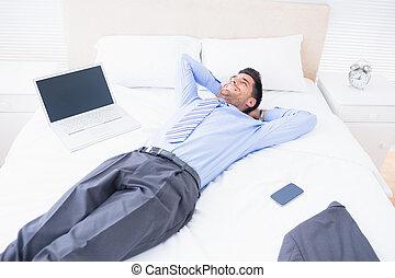 homem negócios, sorrindo, seu, mentindo, cama