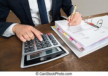 homem negócios, usando, calculadora, enquanto, verificar, fatura, escrivaninha