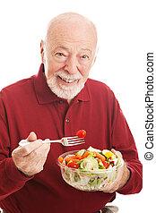 homem sênior, come, salada