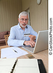 homem sênior, fazendo compras online