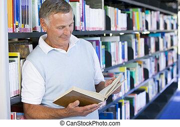 homem sênior, leitura, em, um, biblioteca