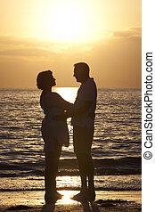 homem sênior, &, mulher, junte praia, em, pôr do sol