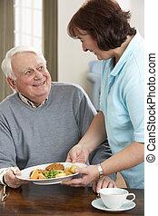 homem sênior, sendo, servido, refeição, por, carer