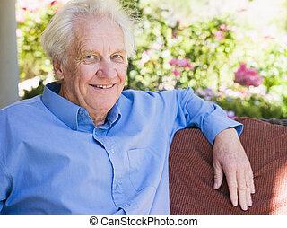 homem sênior, sentando, ao ar livre