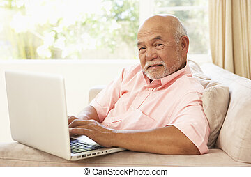 homem sênior, usando computador portátil, casa