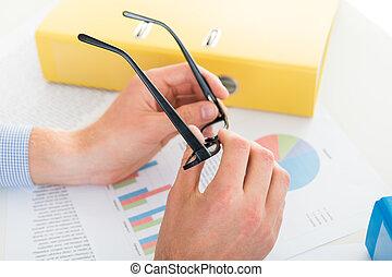 homem, segurar óculos, ligado, a, escrivaninha, em, escritório