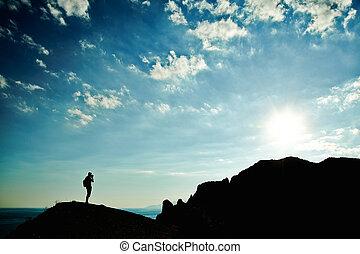 homem, silueta, em, pôr do sol, em, montanhas