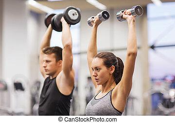 homem sorridente, e, mulher, com, dumbbells, em, ginásio