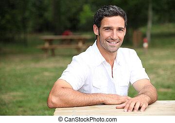 homem sorridente, em, um, banco parque