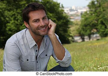 homem sorridente, parque, sentando