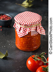 Homemade adjika with tomatoes in jar on dark background.