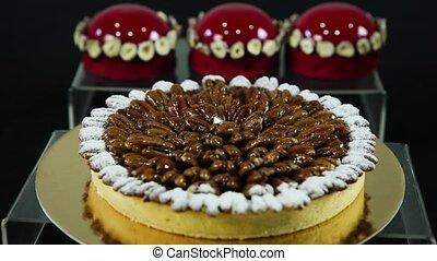 homemade almond coated tart lie against red glazed dessert -...
