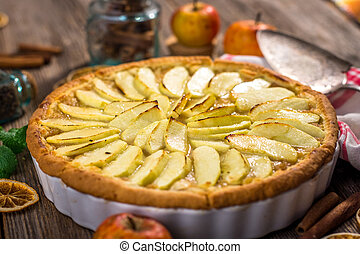 Homemade apple pie and ingredients on a rustic table