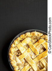 Homemade apple pie on a black wooden background, top view. Flat lay, overhead, from above. Copy space.