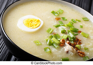 Homemade Asian rice soup with chicken, vegetables and egg close-up. horizontal
