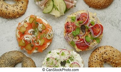Homemade Bagel sandwiches with different toppings, salmon, ...