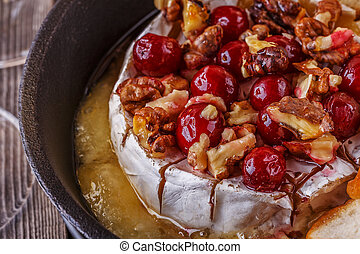 Homemade baked brie with honey, cranberry and walnut, selective focus.