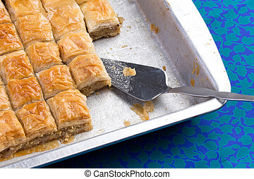 Home made baklava ready to serv from aluminum tray with brushed stailes-steel spatula