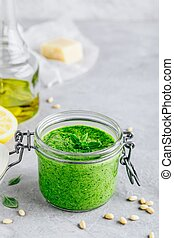 Homemade basil pesto sauce in glass jar with parmesan cheese and olive oil