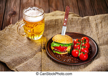 Homemade beef burger and fresh vegetables on Clay dish with glass of beer on rustic wooden table, copy space