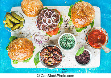 Homemade beef burgers served with pickles, spices, tomato sauce