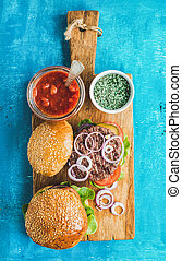 Homemade beef burgers with onion, fresh vegetables, spices, tomato sauce