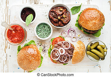 Homemade beef burgers with onion, pickles, vegetables, sun-dried tomatoes, sauce