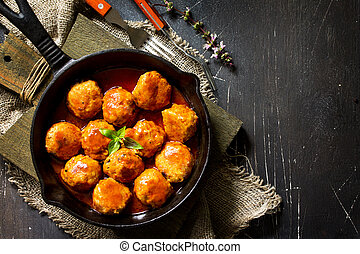 Homemade Beef meatballs in tomato sauce in a frying pan on dark stone table.  Flat lay, top view background. Copy space.