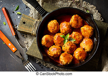 Homemade Beef meatballs in tomato sauce in a frying pan on dark stone table.  Flat lay, top view background.