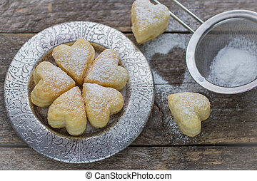 homemade biscuits in the form of hearts on wooden table. shallow depth of field
