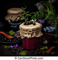 Jar of delicious homemade black currant curd (jam) on dark background