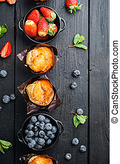 Homemade blueberries muffins, on black wooden table background, top view flat lay with copy space for text