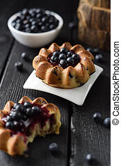 Homemade blueberry cakes with raw forest blueberries on black background. Low key still life with natural lighting
