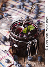 homemade blueberry jam in a glass jar close up on the table. vertical