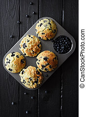 Homemade blueberry muffins and raw blueberries on black background with natural lighting top view