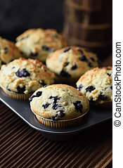 Homemade blueberry muffins on oak board close up with natural lighting side view